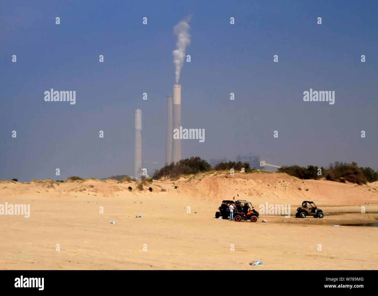 Dune buggies on Zikim Beach on Mediterranean coast in Israel sit in front of the Rutenberg Power Plant smoke stacks. Stock Photo