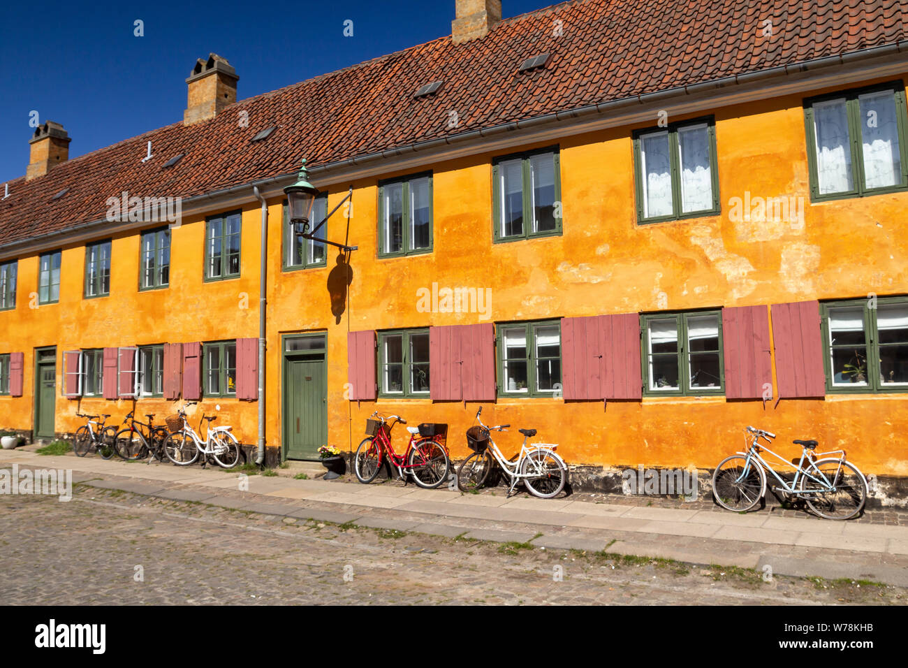 Historic row yellow houses in Nyboder neighborhood in Copenhagen, a former Naval district with bikes in front of the houses Stock Photo