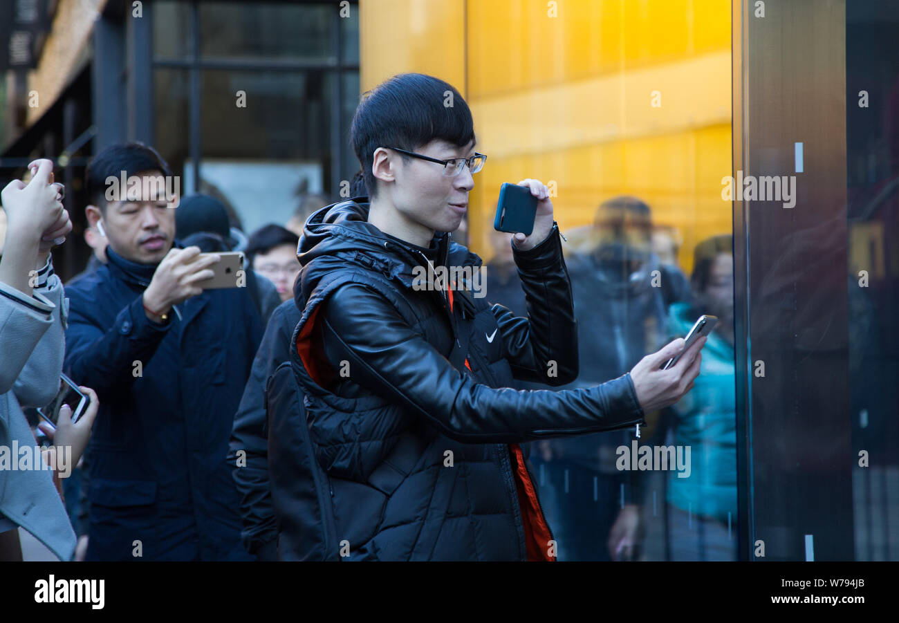 A customer takes photos of his new iPhone X smartphone in front of an Apple store in Beijing, China, 3 November 2017.   The company's highly anticipat Stock Photo