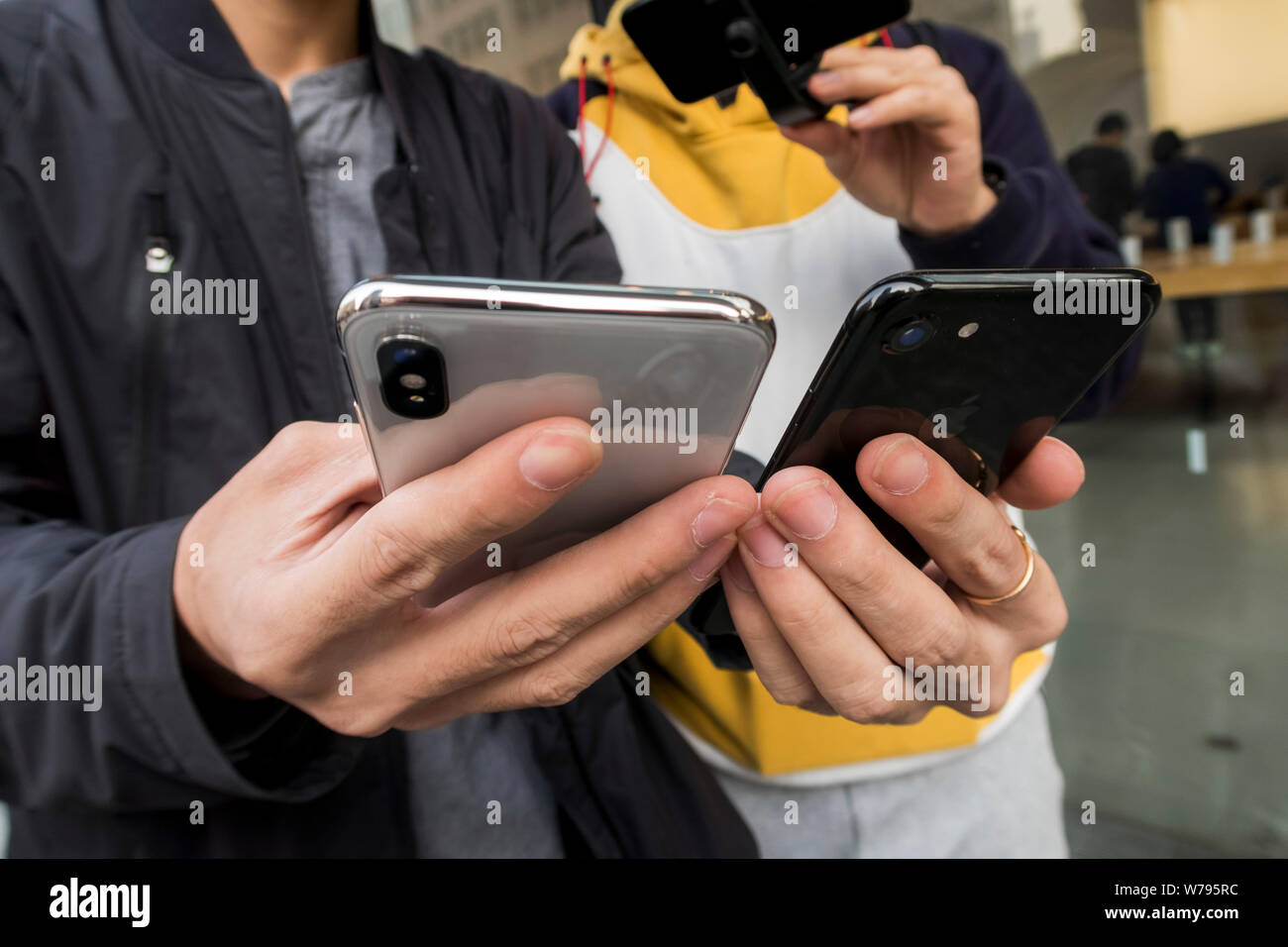 A Chinese customer is making an registration on his new iPhone X smartphone, right, in front of an Apple store in Shanghai, China, 3 November 2017. Stock Photo