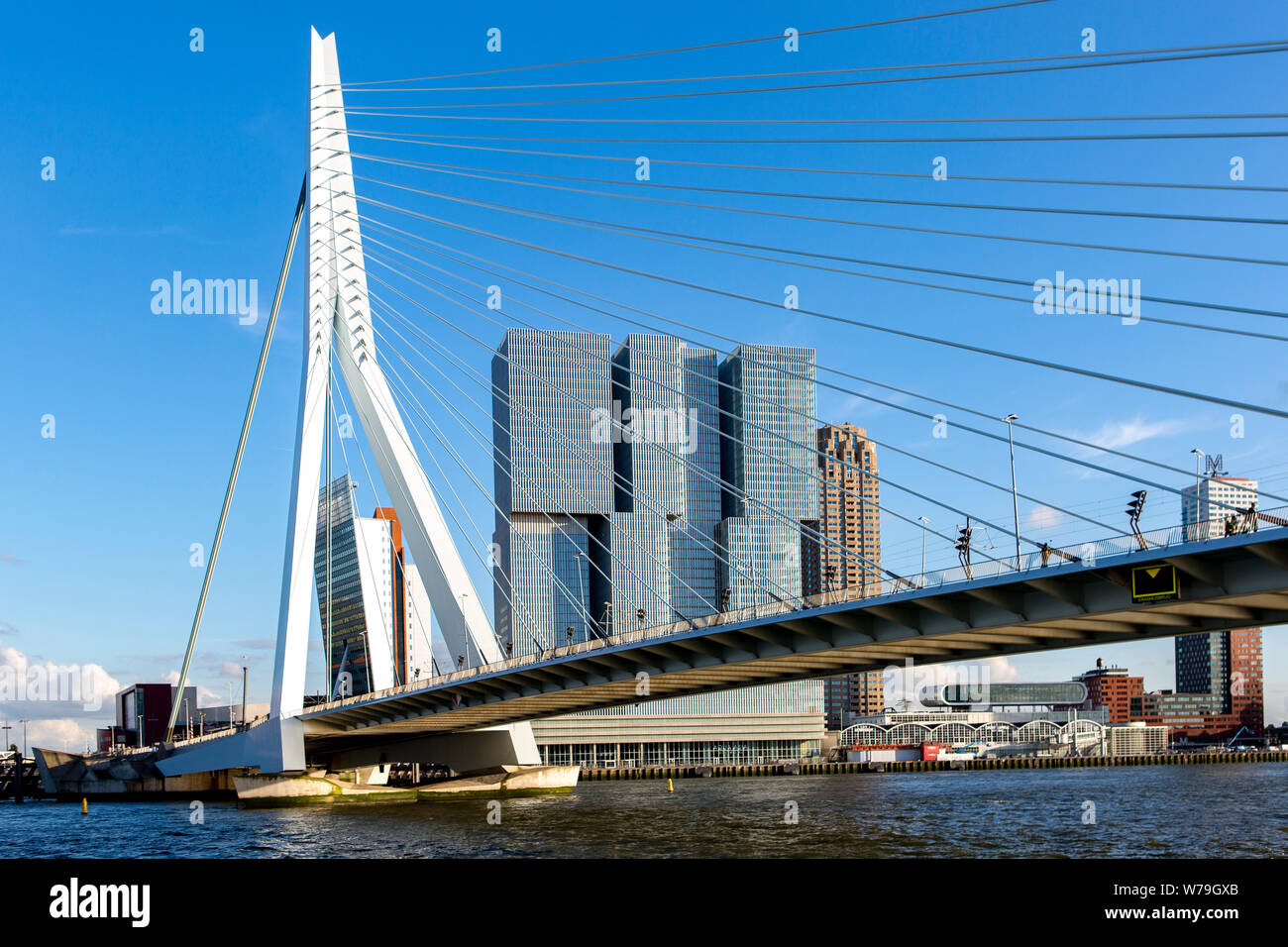 Cityscape of Rotterdam at sunset with the Erasmus bridge in the foreground and high rise buildings of the financial district in the Dutch city Stock Photo