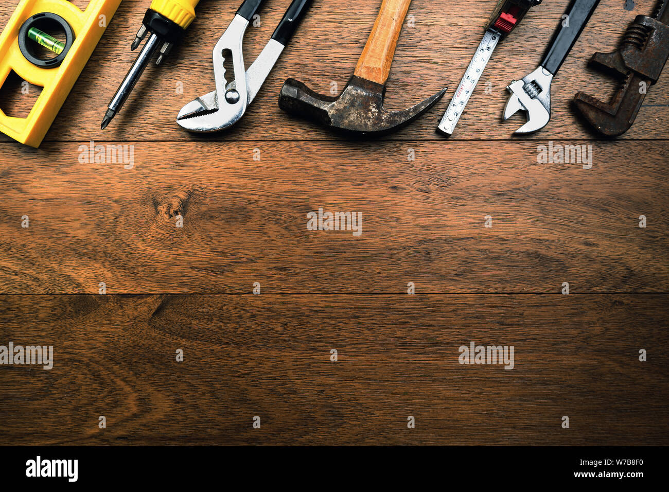 Grungy rusty craftsmen Tools like water scale, pliers, screwdriver, Hammer and tape measure on wooden planks with room for writing Stock Photo