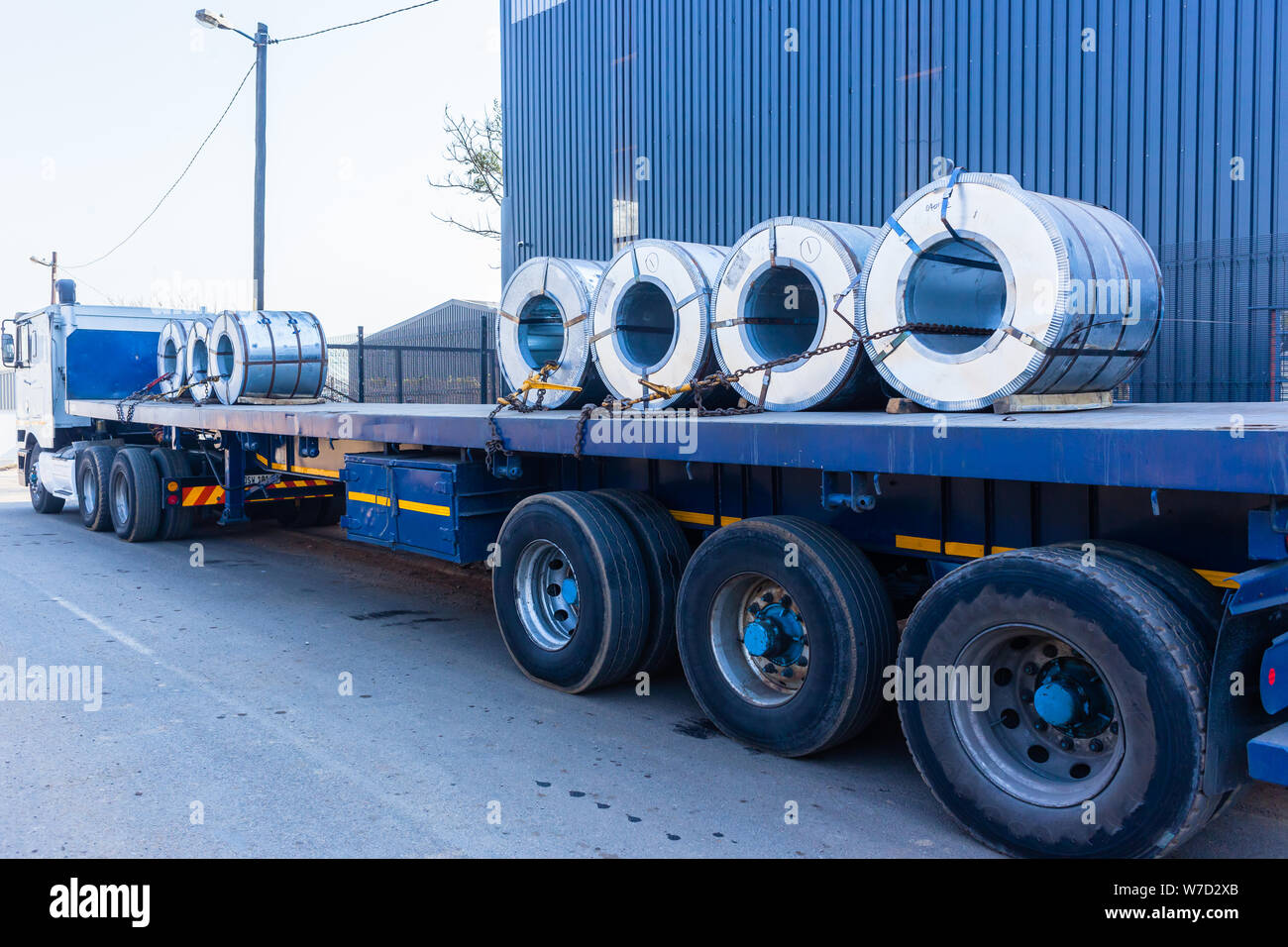 Truck transporting heavy steel sheet rolls secured on trailer from refinery to warehouse for customer manufacturing. Stock Photo