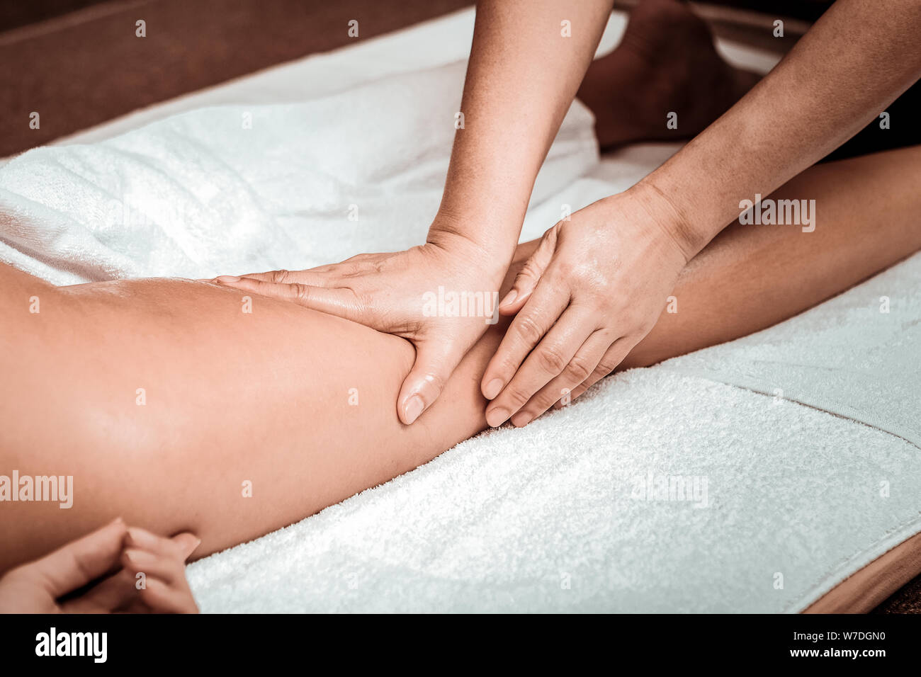 Masseuse doing oil massage of clients hips. Stock Photo