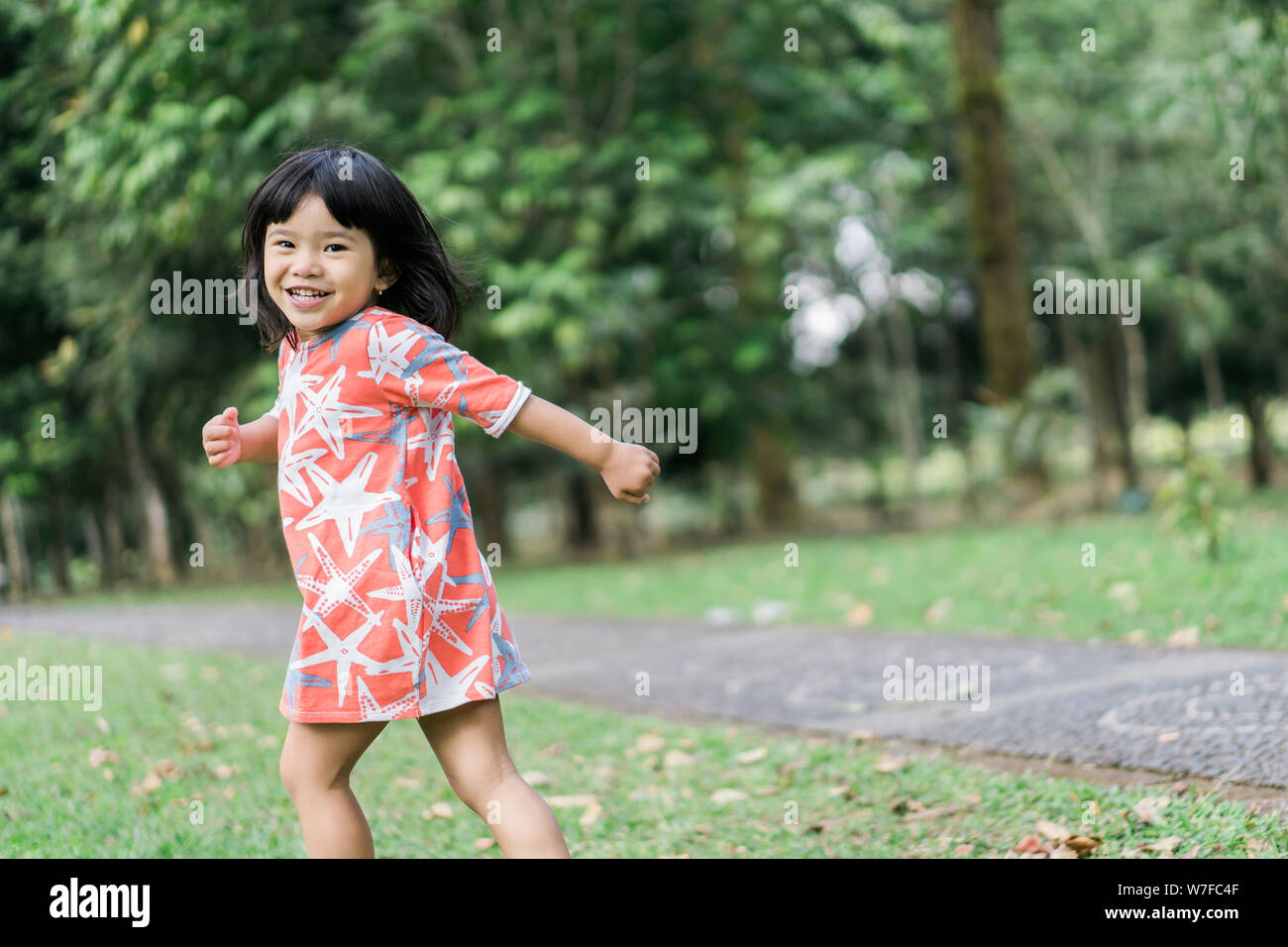 Asian Cute Girl With Smile Enjoy Playing Alone Stock Photo