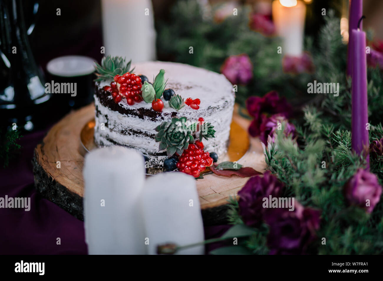 Delicate Wedding White Cake Decorated With Pomegranate And Succulent Surrounded By Flowers And Candles Stock Photo Alamy