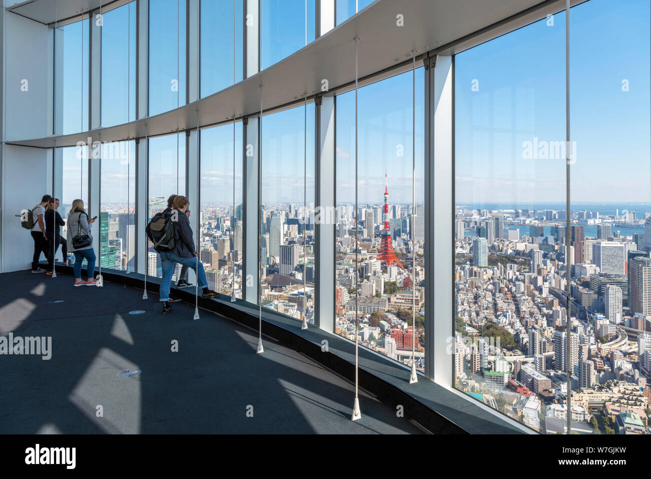 Visitors looking out over the city from the observation deck of the Mori Tower, Roppongi Hills, Tokyo, Japan Stock Photo