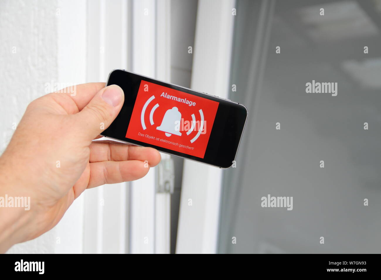 """Mobile phone with a picture alarm system and the text """"Alarm"""" Stock Photo"""