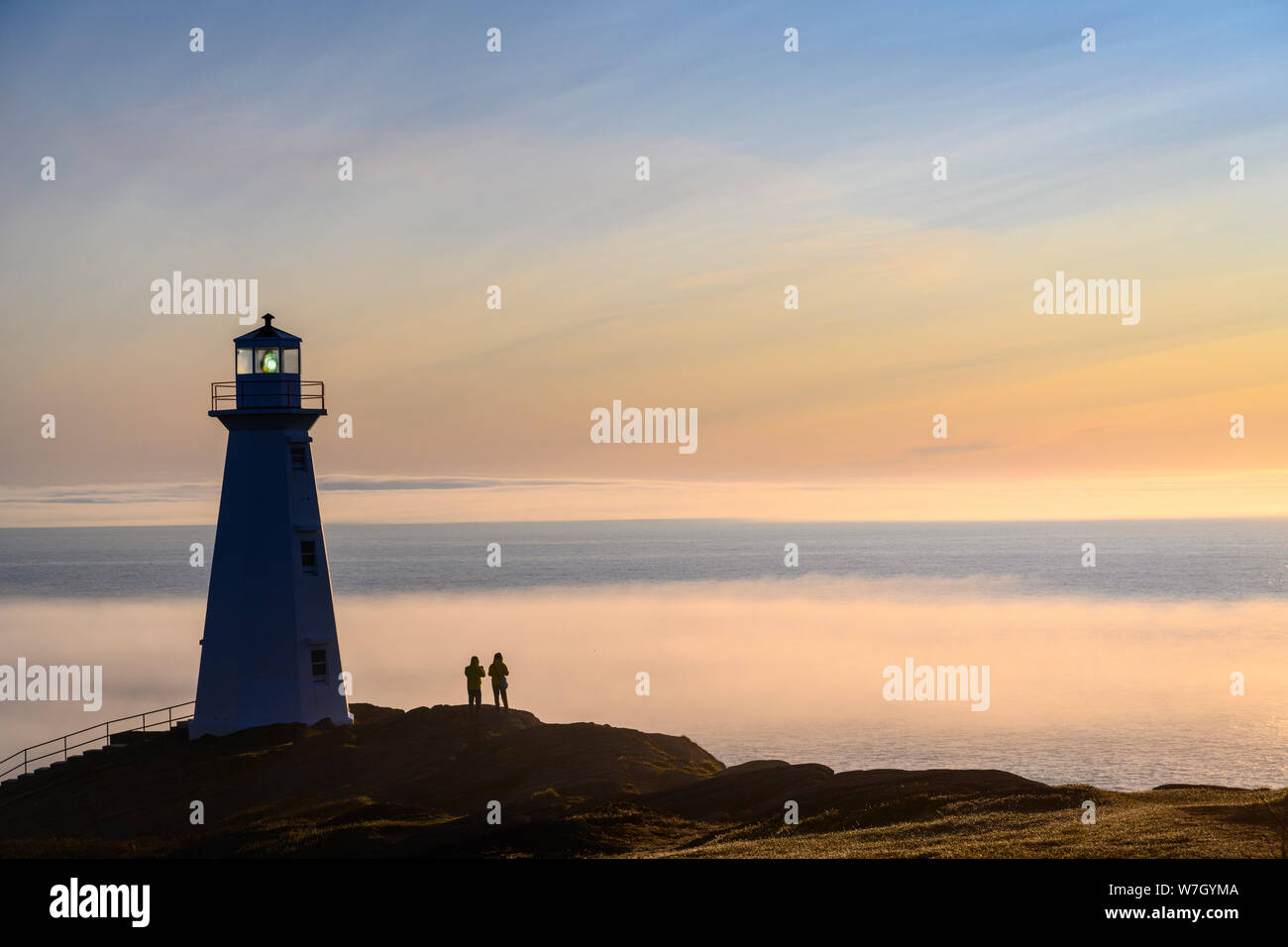 Visitors at Cape Spear Lighthouse with fog bank over the Atlantic Ocean;  St. John's, Newfoundland, Canada. Stock Photo