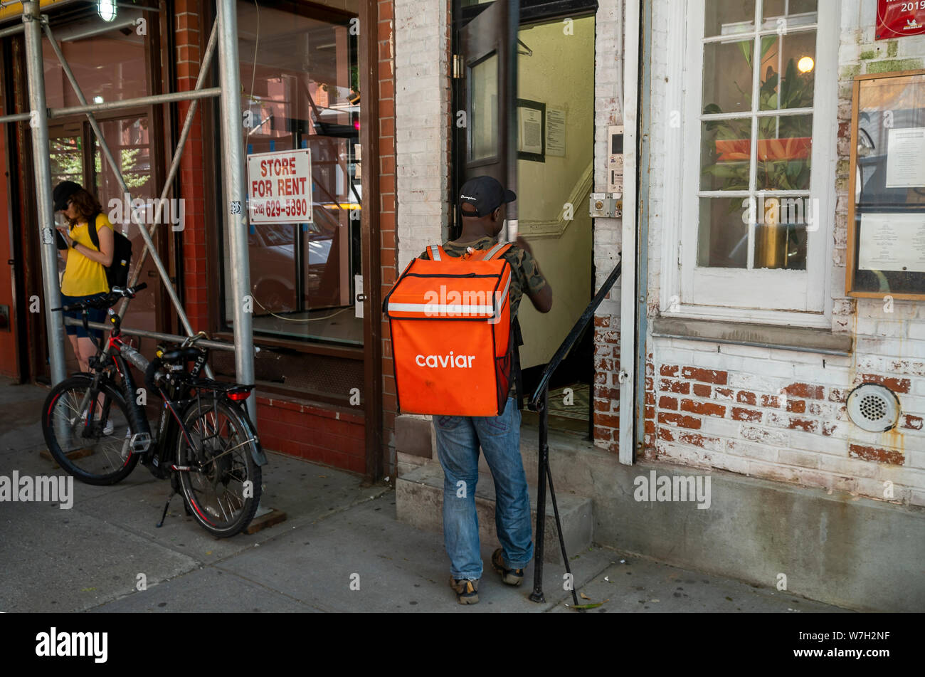 A Caviar delivery worker outside a building in New York on Saturday, August 3, 2019. Square has sold their food delivery service Caviar ot DoorDash in a $410 million deal. (© Richard B. Levine) Stock Photo