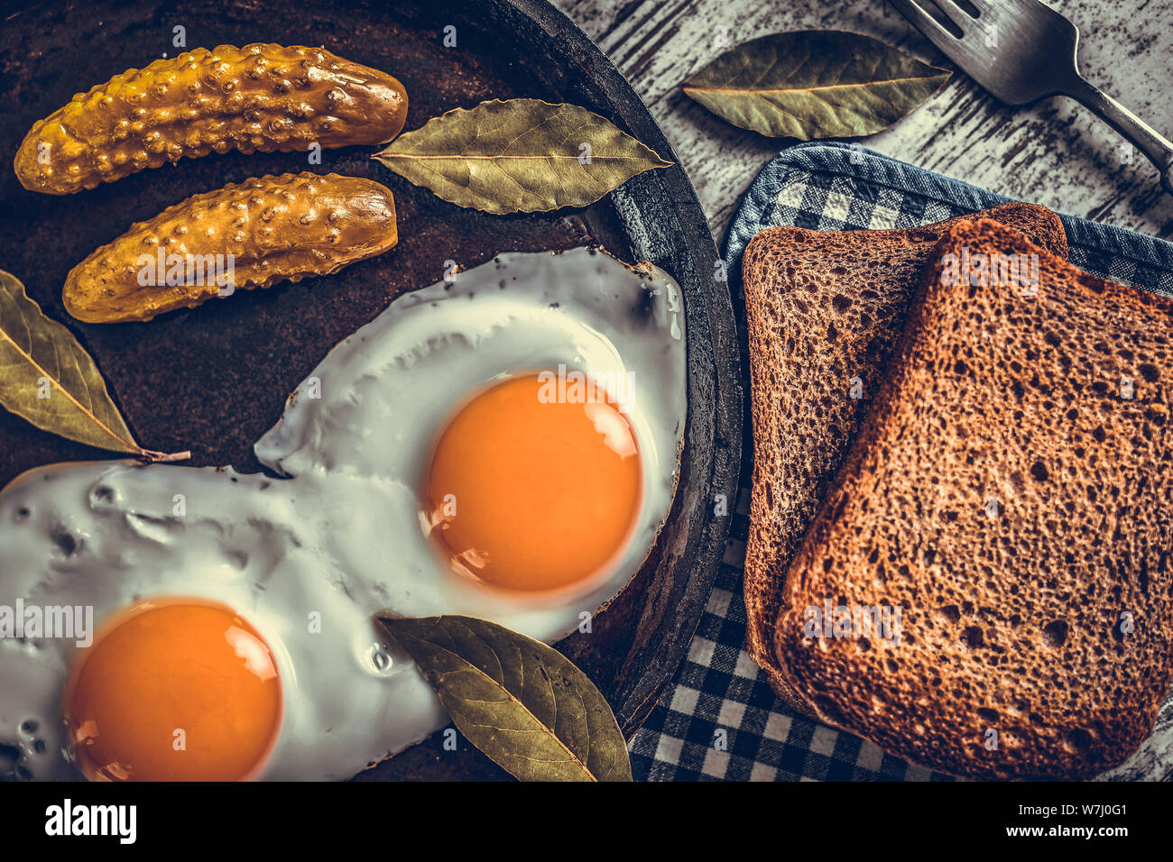 Fried eggs in a frying pan. Rye toast and pickled cucumber next to fried eggs. Stock Photo