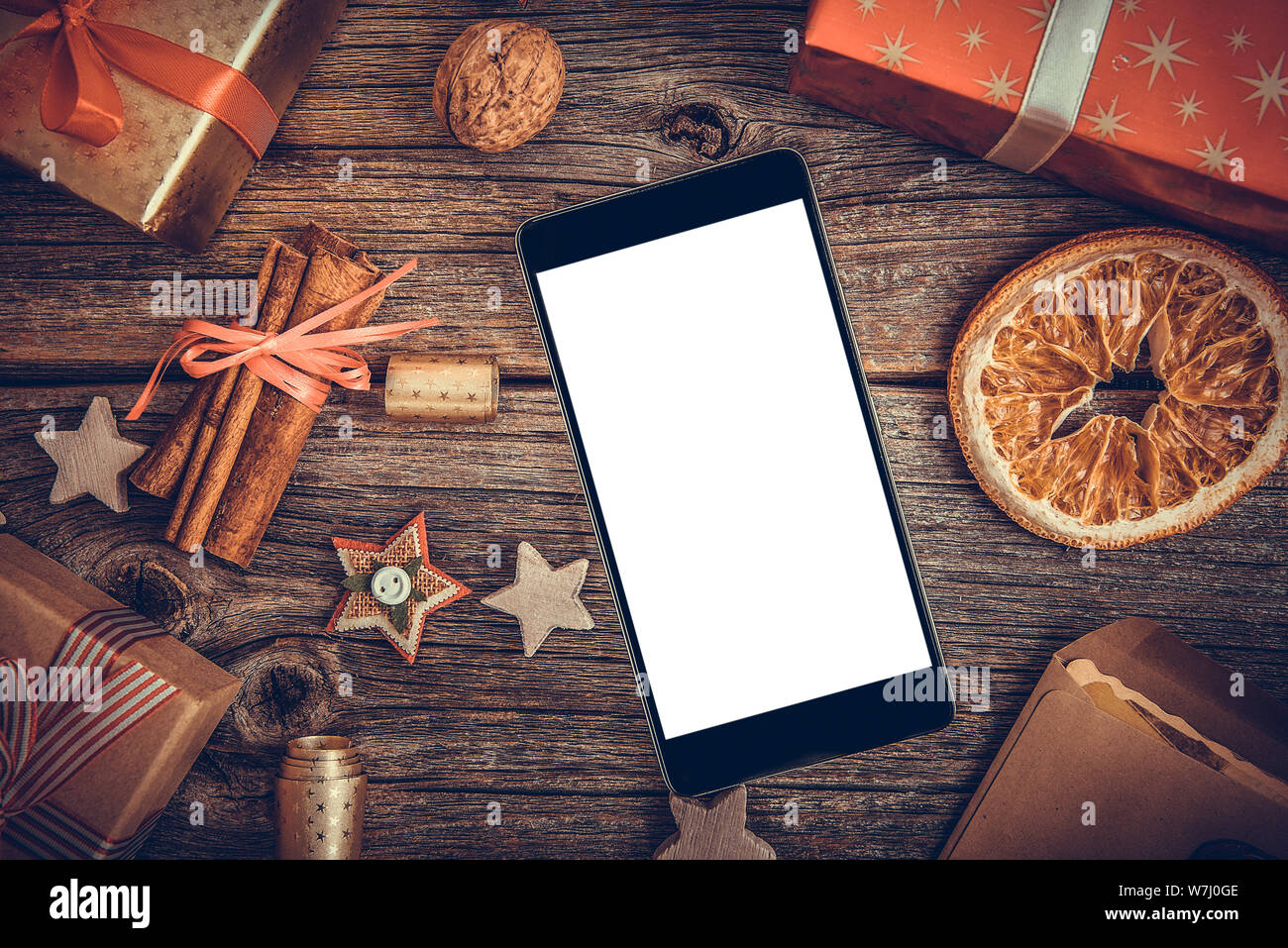 Smartphone on a wooden table with a variety of New Year winter decorations. Stock Photo