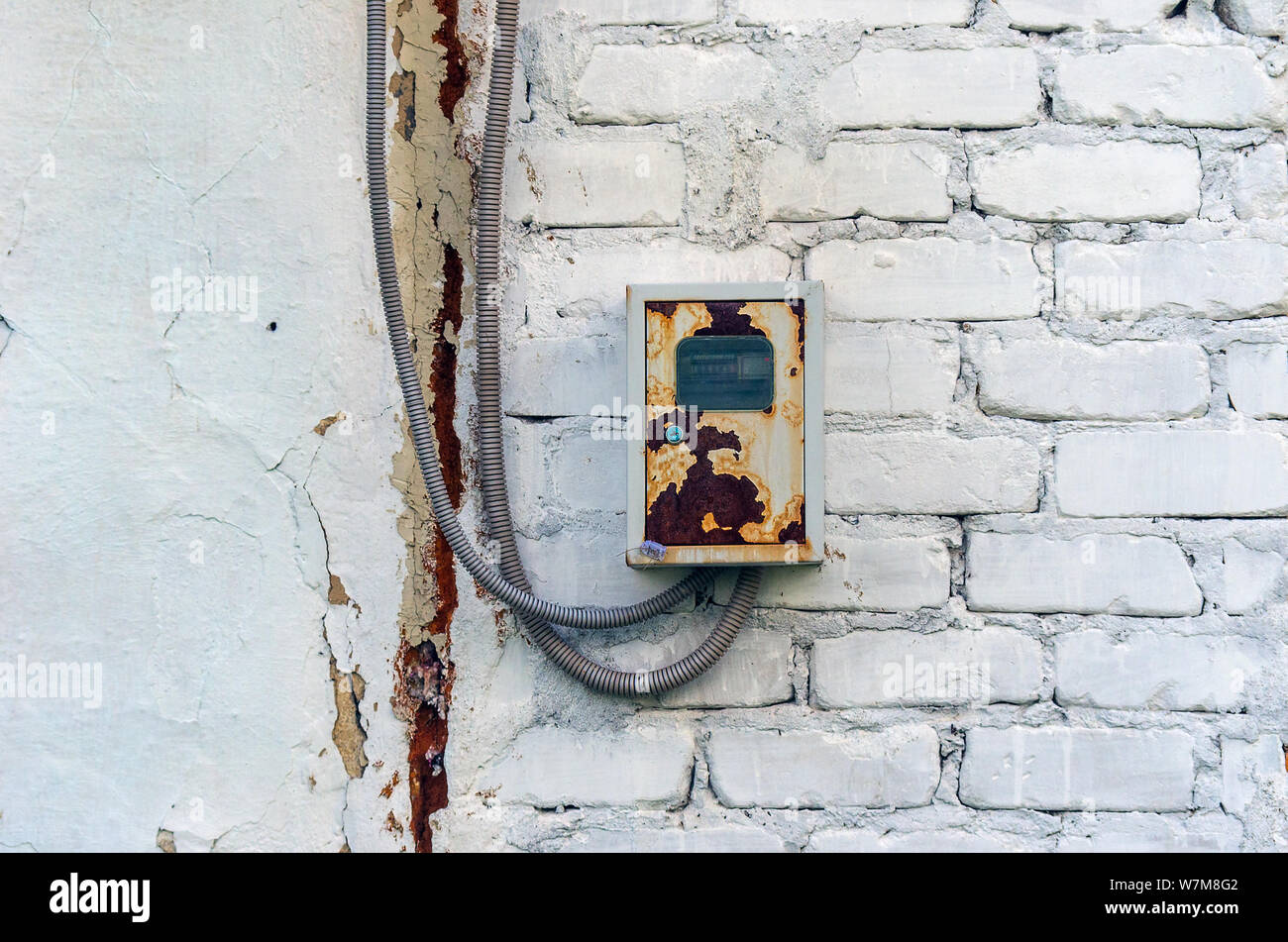 Rusty Distribution Board Metal Box with Electricity Meter, Seal and Two Cables in Steel Coil Housing on a White Brick Wall Outdoors. Stock Photo