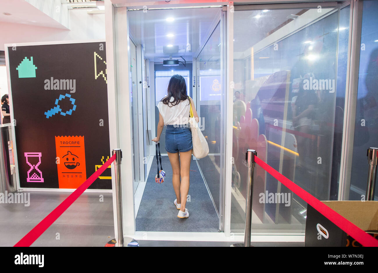 A customer pays her purchase as she walks through a door that can automatically deduct the payment at the Alibaba's Taocafe, a store without cashier a Stock Photo