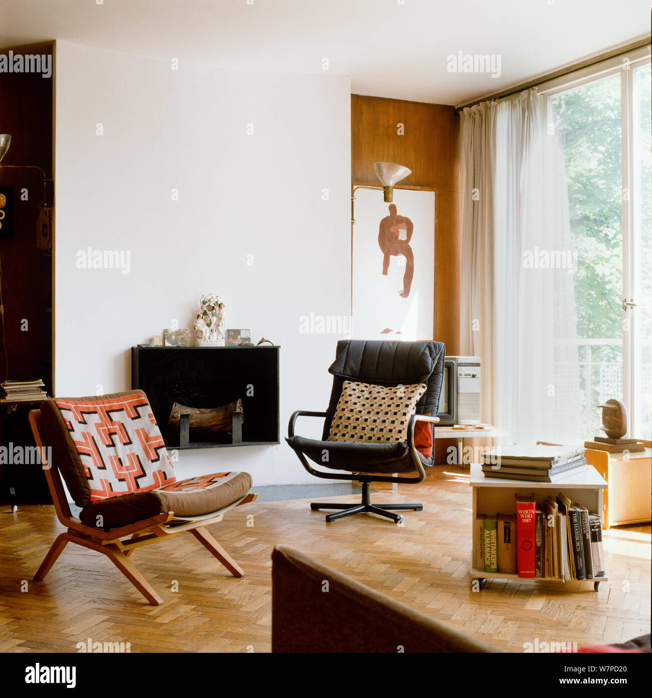 Chairs by fireplace in retro living room Stock Photo - Alamy