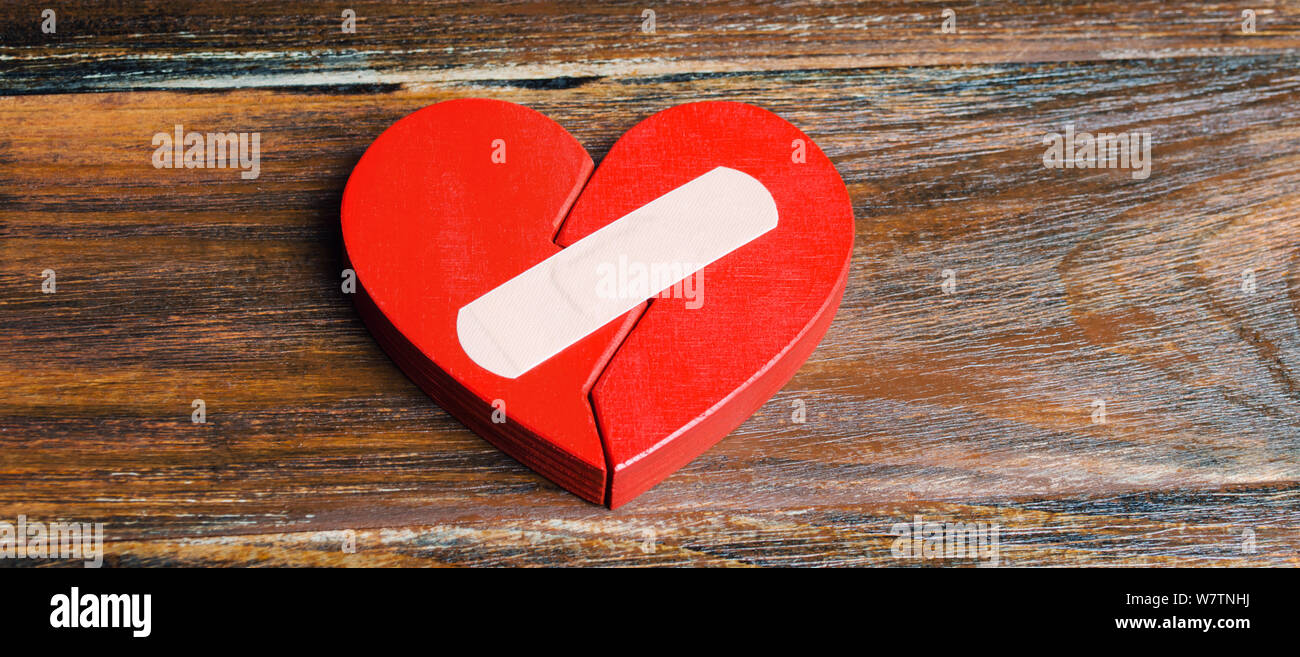 A red heart with a plaster. Renewal of the relationship. Family psychotherapist services. Reconciliation. Saving the family. Search for compromises. C Stock Photo