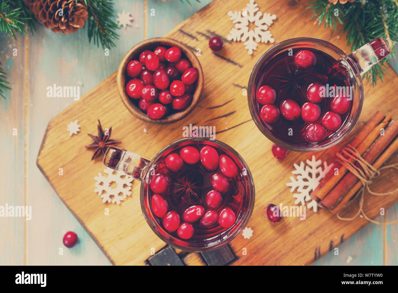 Christmas, Thanksgiving drinks. Hot winter drink with cranberries and cinnamon on wooden table. Top view flat lay. Toned image. Stock Photo