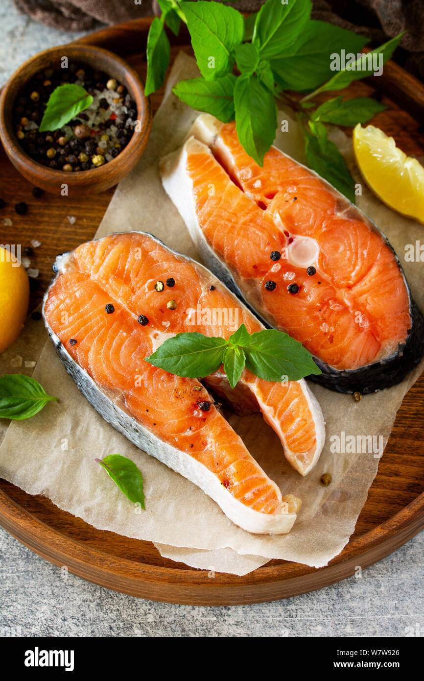 Steak raw fish prepared for cooking. Salmon wiht basil and spices on slate table. Stock Photo