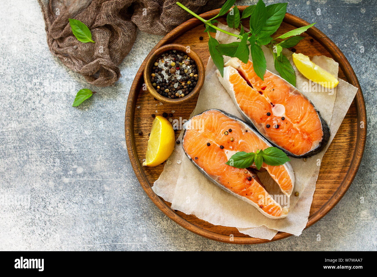 Steak raw fish prepared for cooking. Salmon wiht basil and spices on slate table. Top view flat lay. Stock Photo