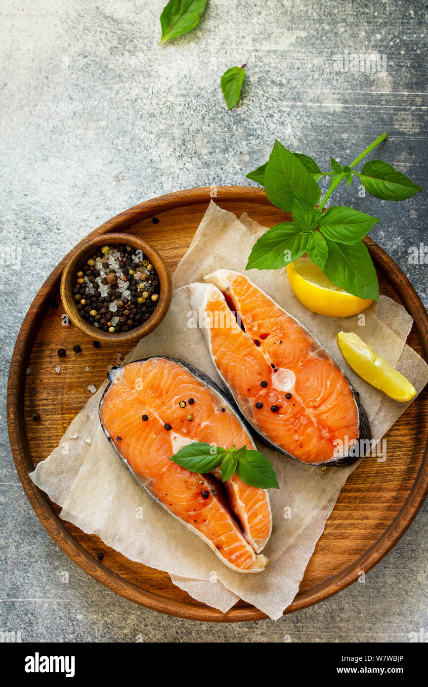 Steak raw fish prepared for cooking. Salmon wiht basil and spices on slate table. Top view flat lay. Free space for your text. Stock Photo