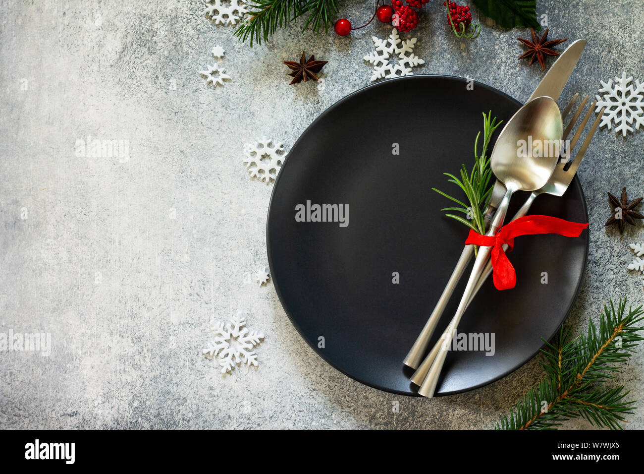 Christmas background. Christmas decoration table. Festive black plate and cutlery with Christmas decor on retro festive table. Top view flat lay. Free Stock Photo