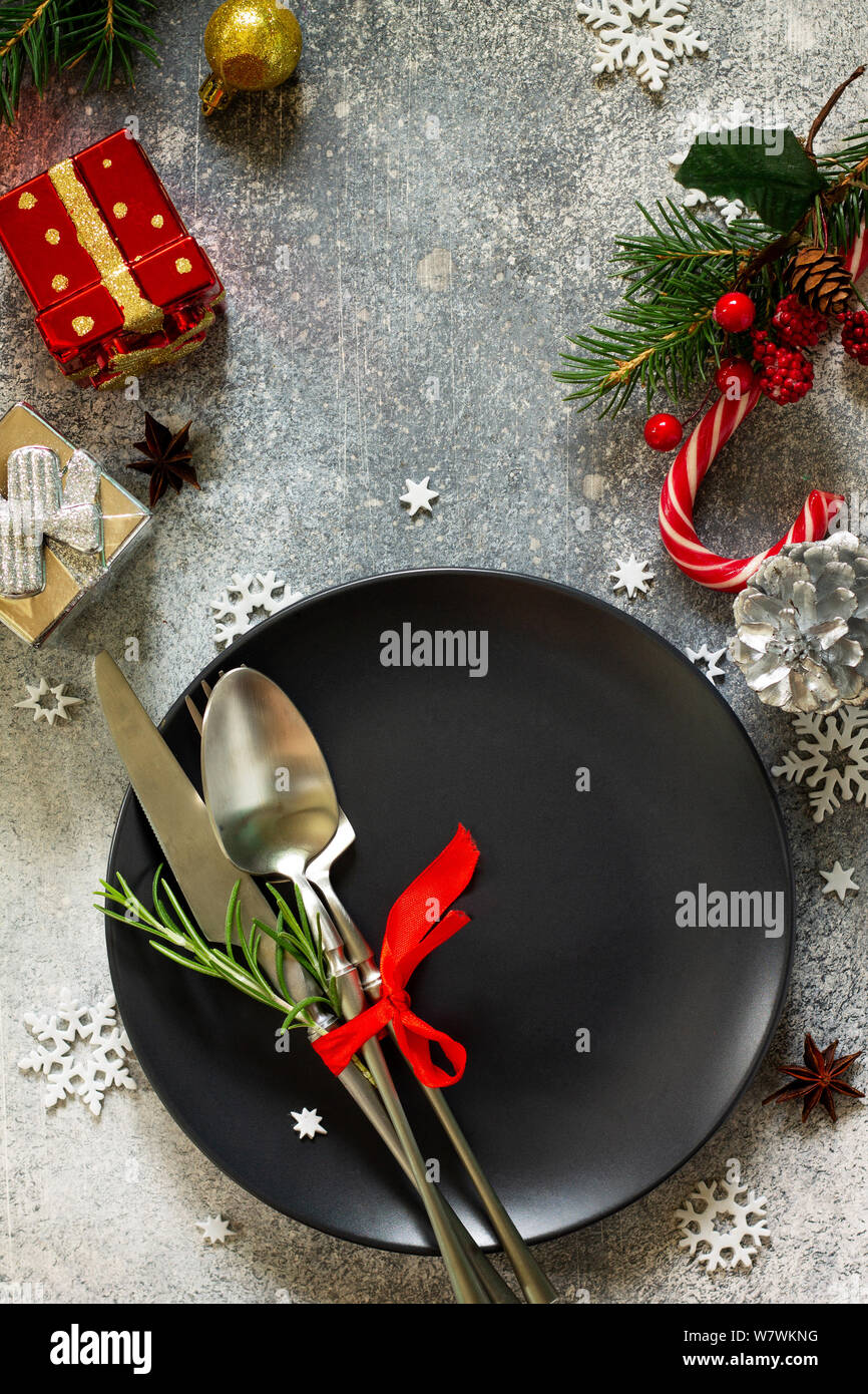 Christmas background. Christmas decoration table. Festive black plate, present and cutlery with Christmas decor on retro festive table. Top view flat Stock Photo