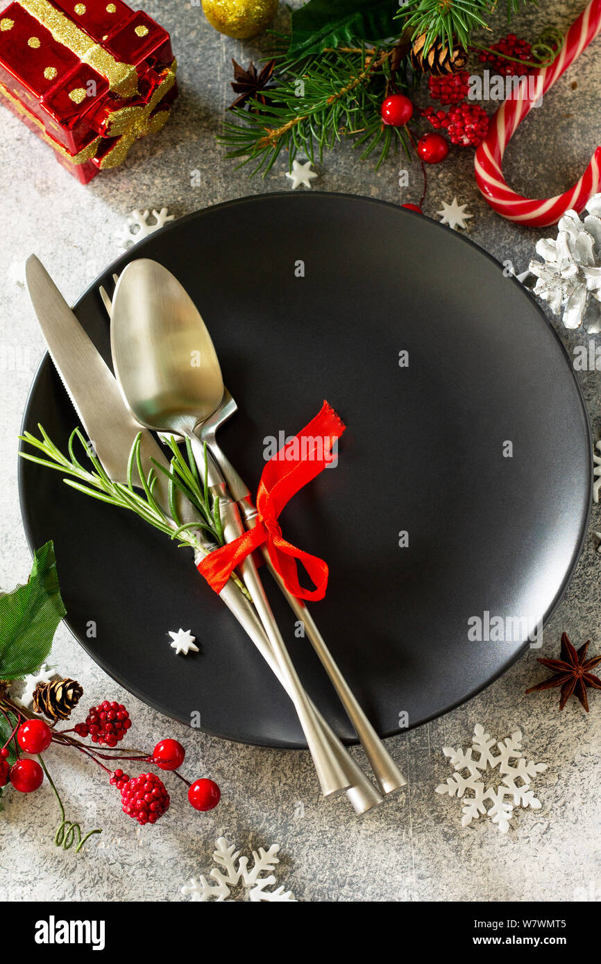Christmas background. Christmas decoration table. Festive black plate and cutlery with Christmas decor on retro festive table. Stock Photo