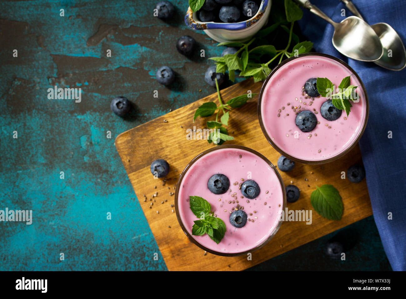 Healthy Chia seed pudding in a glass with blueberry on slate table. Healthy breakfast, vitamin snack, diet and healthy eating. Top view flat lay. Free Stock Photo
