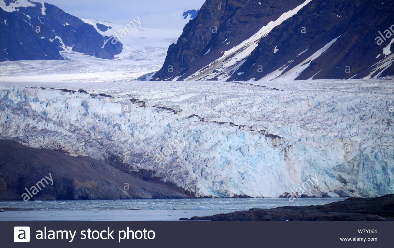 Svalbard, Arctic Circle, in summer. Dramatic view of glaciers and melting snow on mountains along the Spitsbergen Coastline, blue skies and sea. Stock Photo