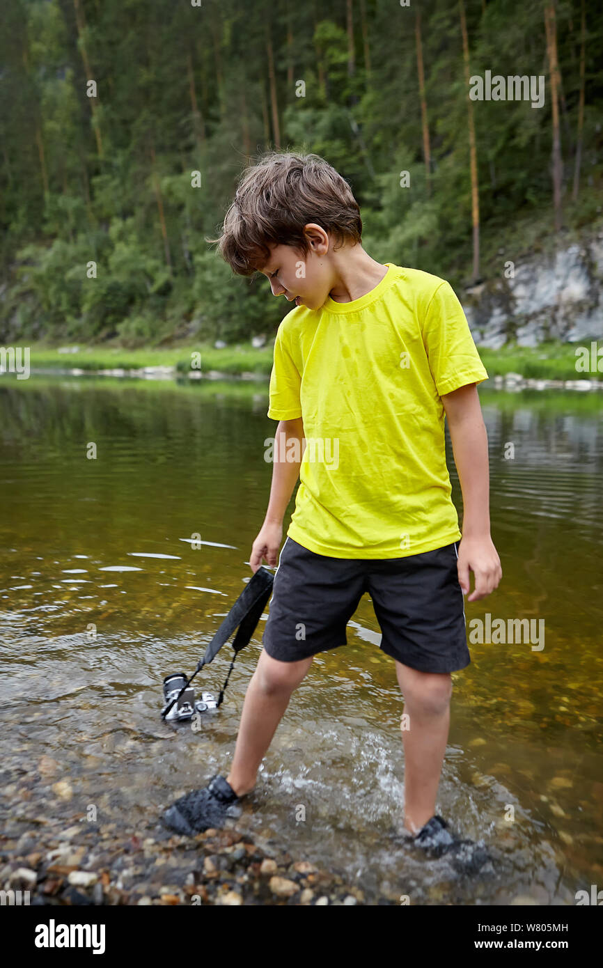 A young bully indulges in the camera of his parents. The boy drowned the camera in the river, and the gadget fell into disrepair, as it was flooded wi Stock Photo