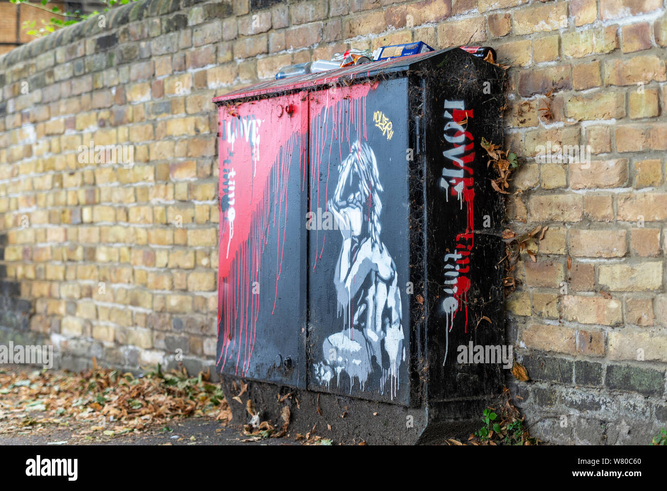 Banksy style artwork of a crying child on a telecommunications junction box, with red paint running down like blood and the words Love Time. Rubbish Stock Photo
