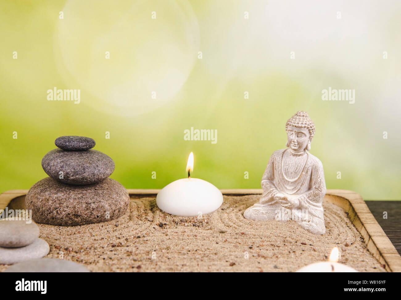 Miniature desk zen sandbox with Buddha figure sit in Lotus position, stacked zen sea stones, spa candles burning against green bokeh studio background Stock Photo