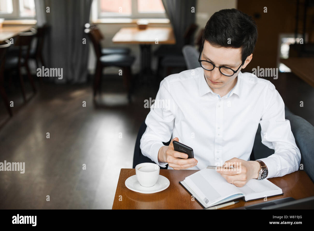 Portrait of confident elegant adult businessman operating with his smartphone while using a holding credit card sitting in a coffee shop working at hi Stock Photo