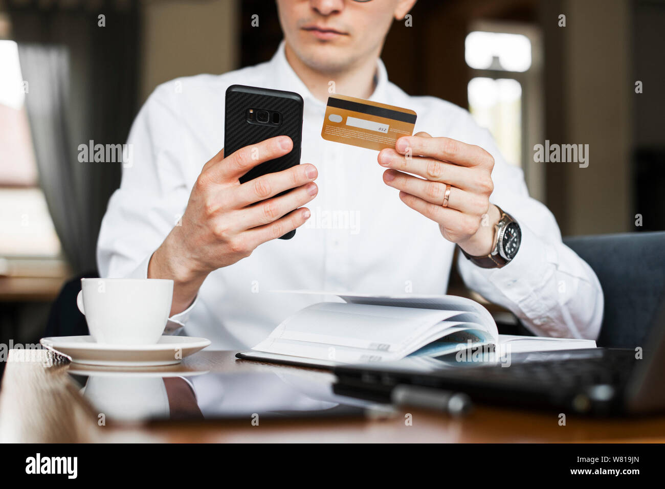 Crop male hands using a smartphone and a gold credit card sitting in a coffee shop . Stock Photo