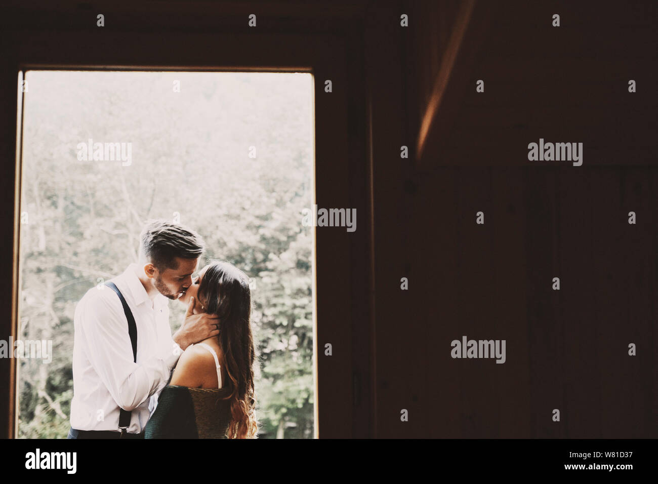 Side View Portrait Of A Lovey Young Married Couple Kissing On The