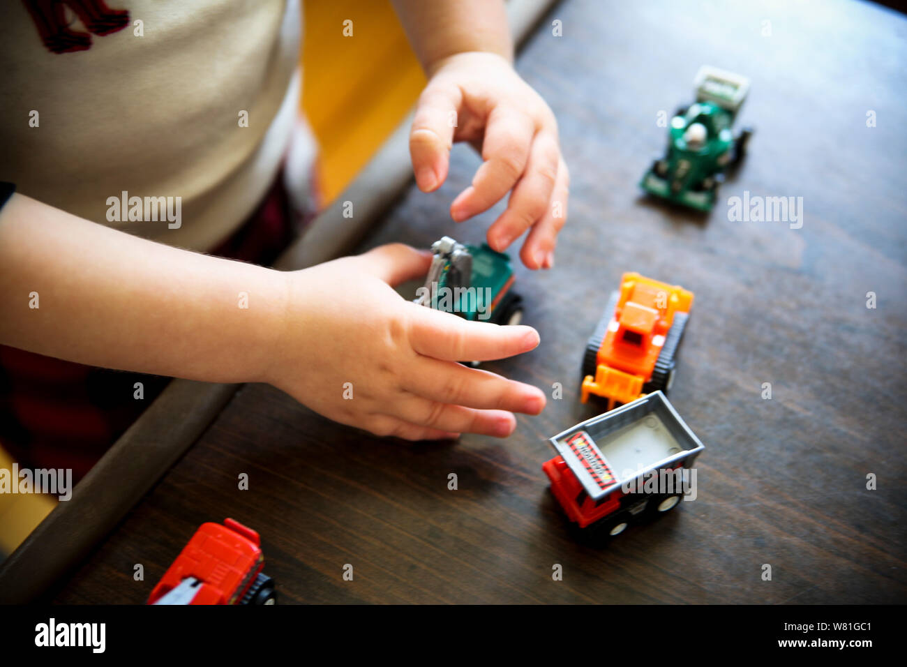 Young Boy Playing with Toy Trucks - Stock Photo