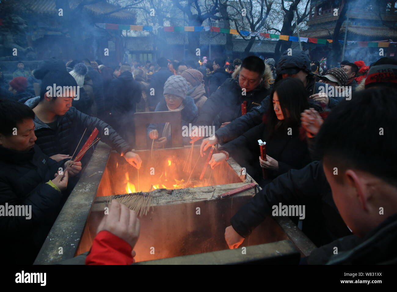 Chinese worshippers burn incense sticks to pray for good