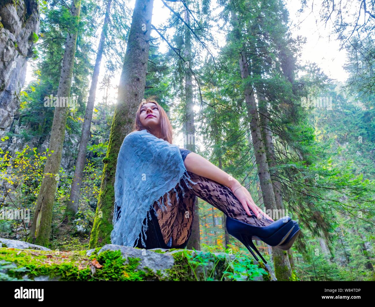 Beautiful young female in nature is sitting in Green forest looking away concerned serious tucked legs spike spiked Black very high-heels sideview Stock Photo