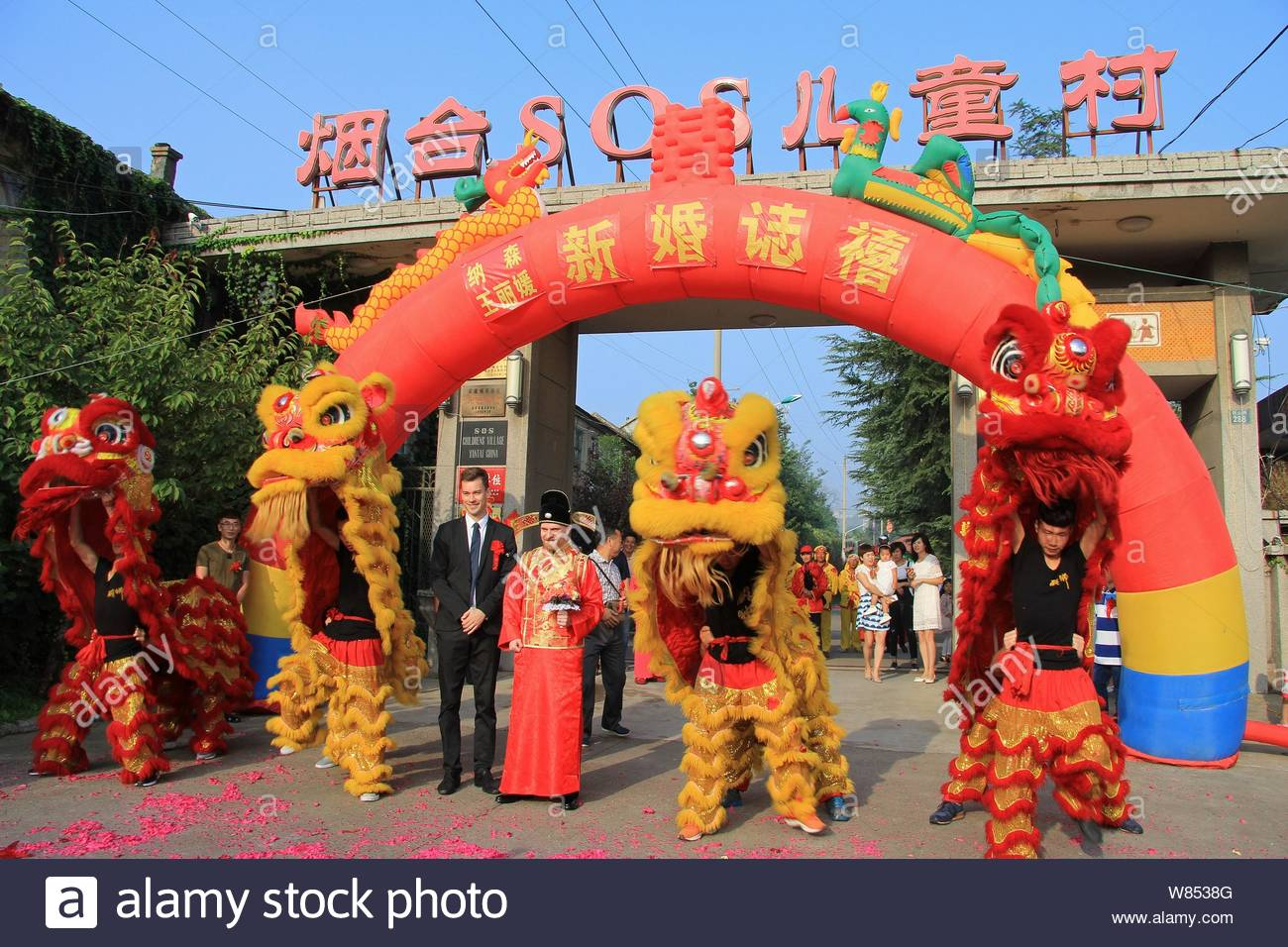 American man Nathan, second left, dressed in traditional Chinese wedding costume, poses with his groomsman during his wedding ceremony at the gate of Stock Photo