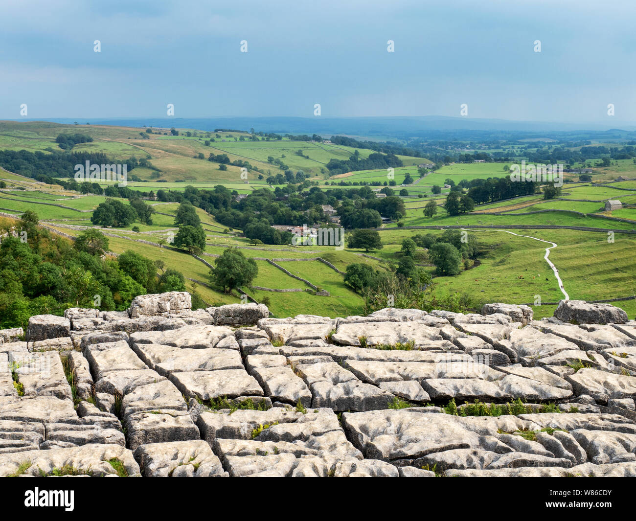 View over malhamdale from the limestone pavement above Malham Cove near Malham Yorkshire Dales National Park England Stock Photo