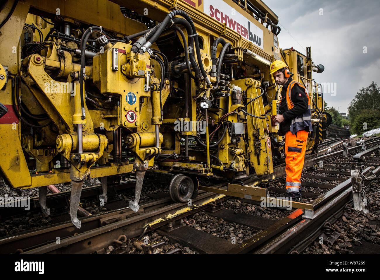 Maintenance team work on London Underground Central Line. Tack defect work grinding and skimming tracks, tamping and redistributing ballast. London UK Stock Photo
