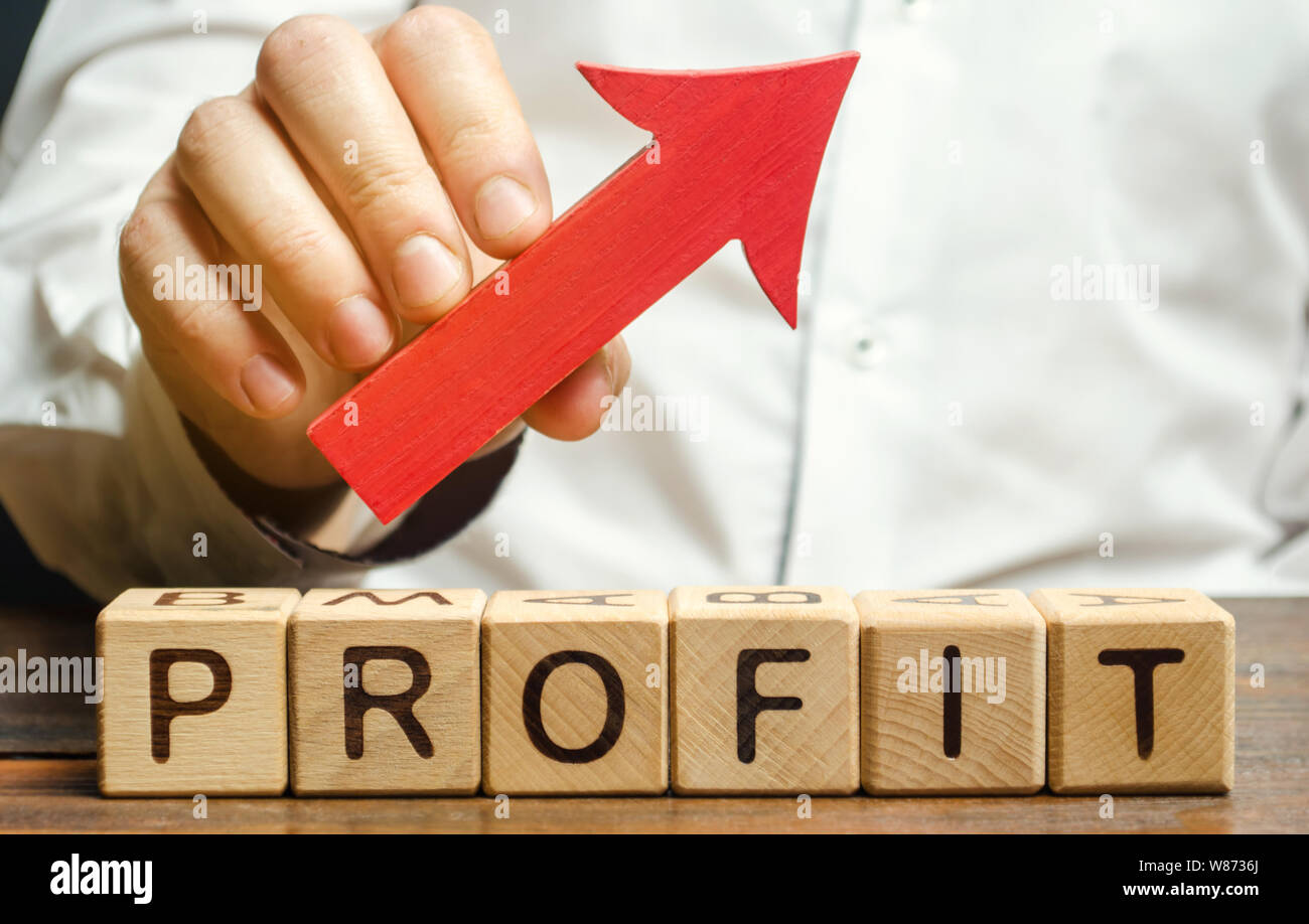Wooden blocks with the word Profit and an up arrow. Concept of business success, financial growth and wealth. Increase profits and investment fund. Pe Stock Photo