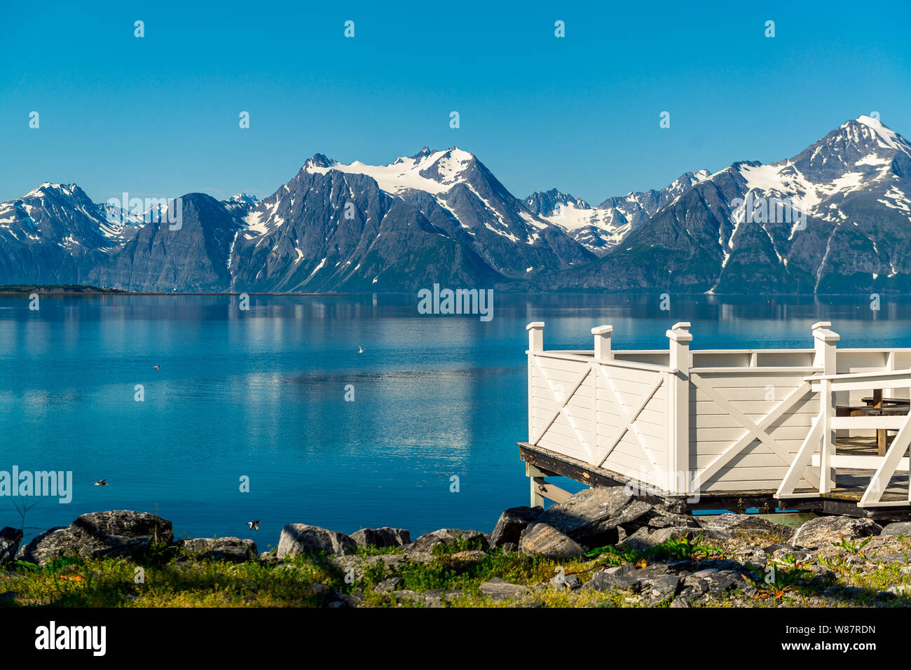 Picnic site rest stop area wooden table decoration and norwegian flag on lake fjord shore. Holidays relaxation on trip. Scandinavia Europe. Stock Photo