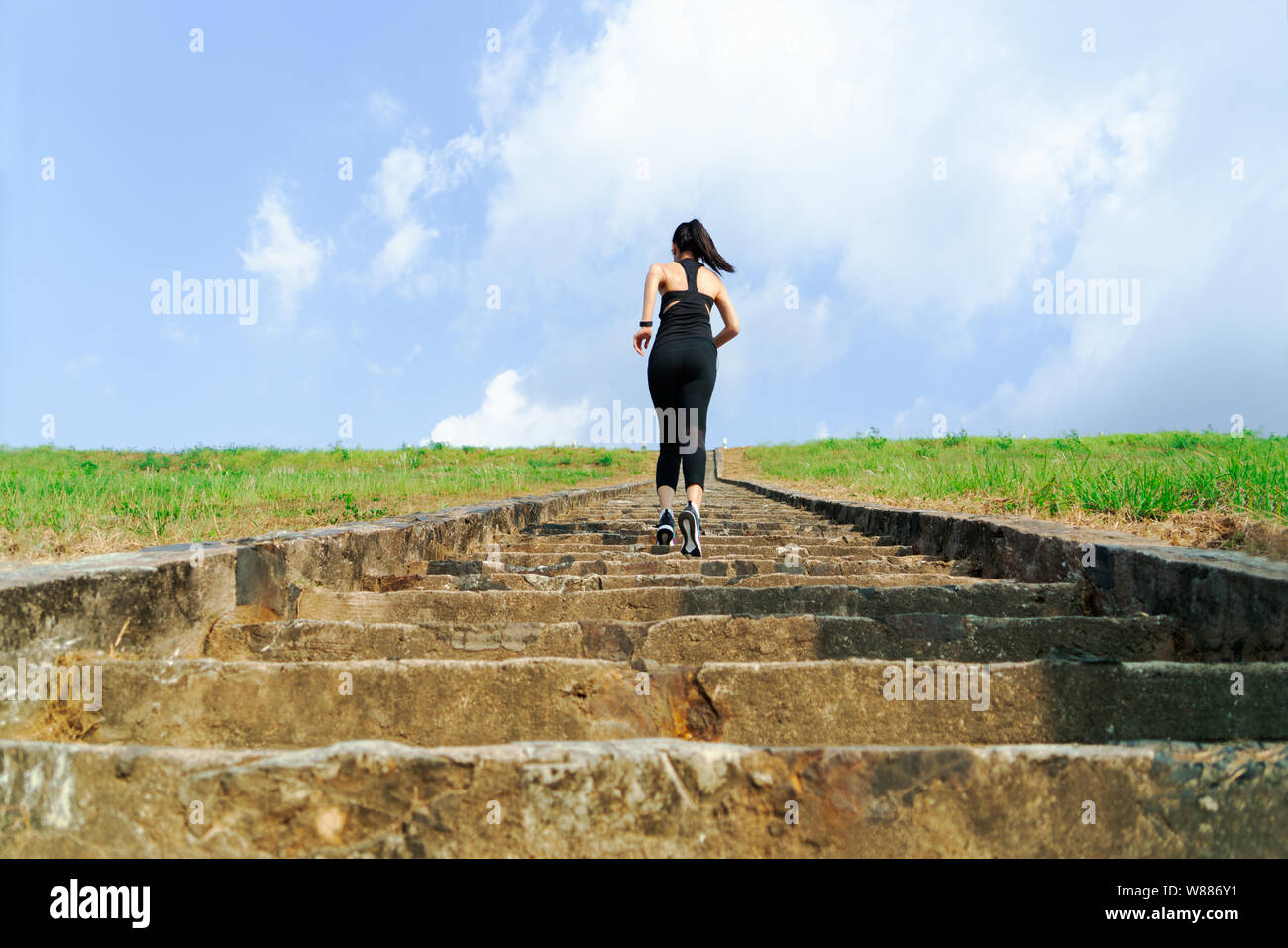 young sport woman running outdoor upstairs on blue sky Stock Photo