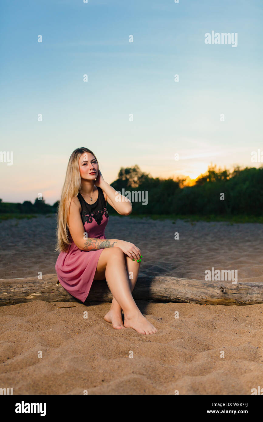 Portrait of the beautiful blond model with long hair on the sand beach Stock Photo