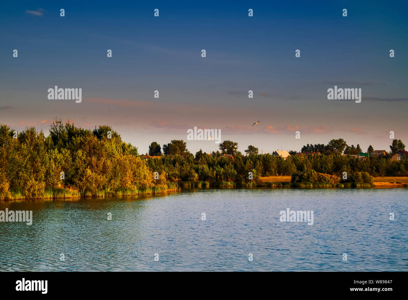 The Russian village on the banks of the river against the backdrop of the setting sun. Stock Photo