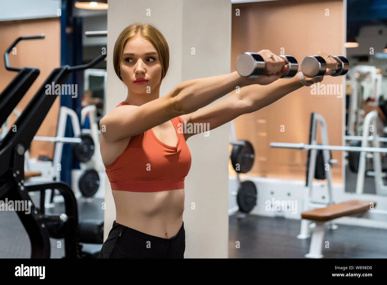 Beautiful young woman trains deltoid in gym Stock Photo