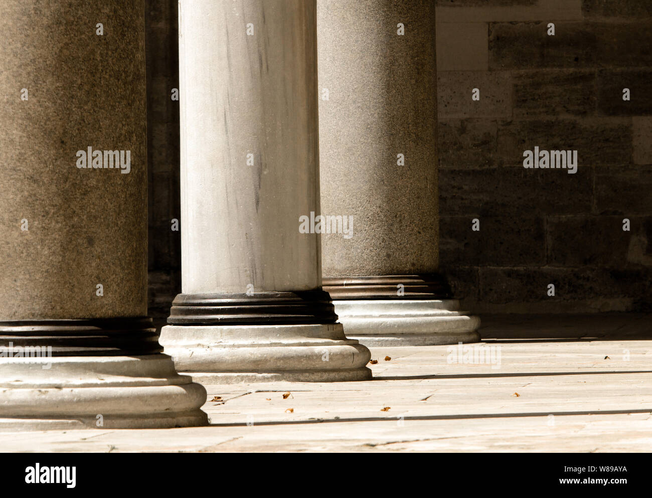 Close up of lower section of three doric order marble columns washed with sunlight in single point perspective image. Stock Photo