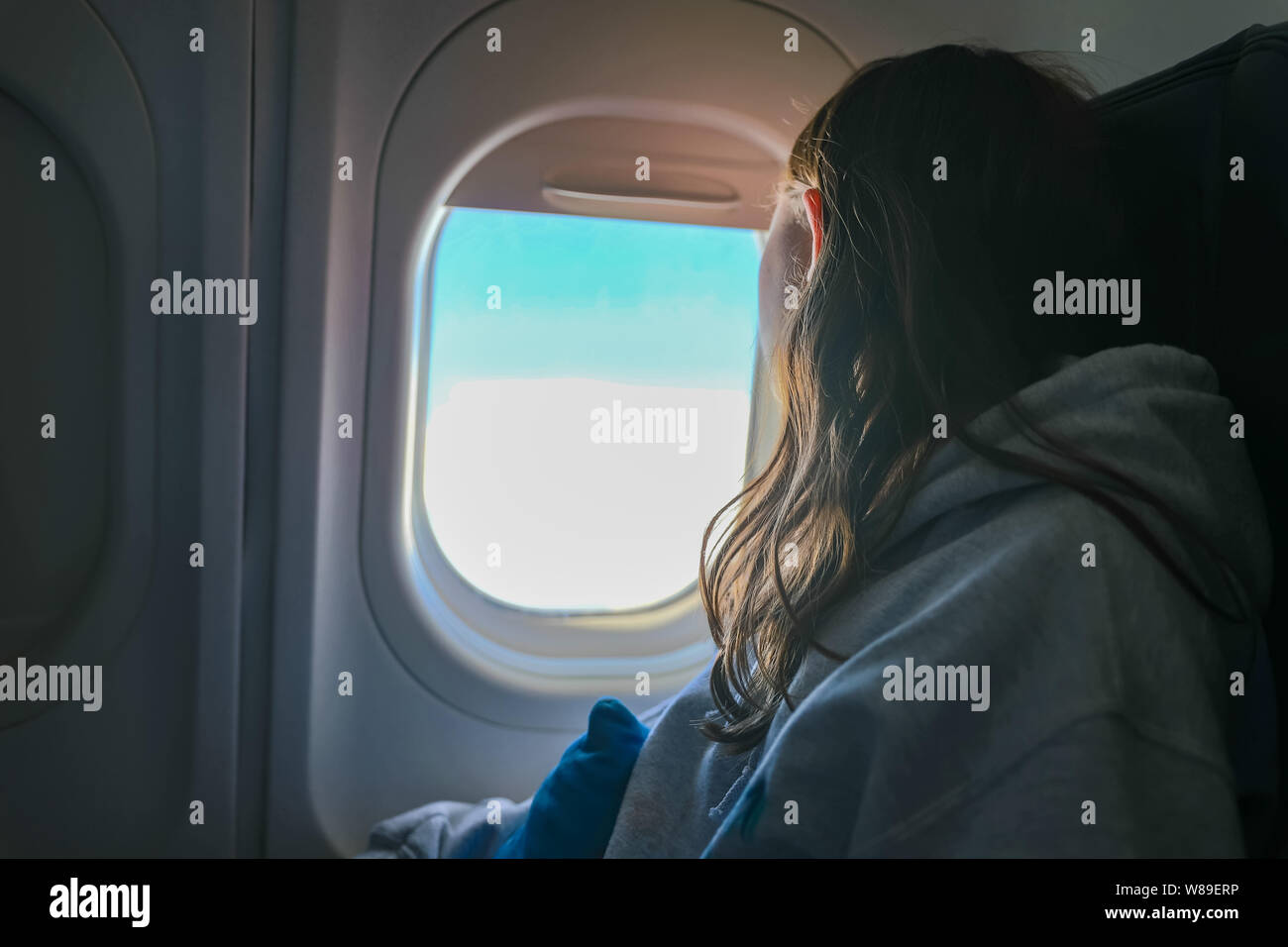Girl looking out airplane window in flight while traveling Stock Photo