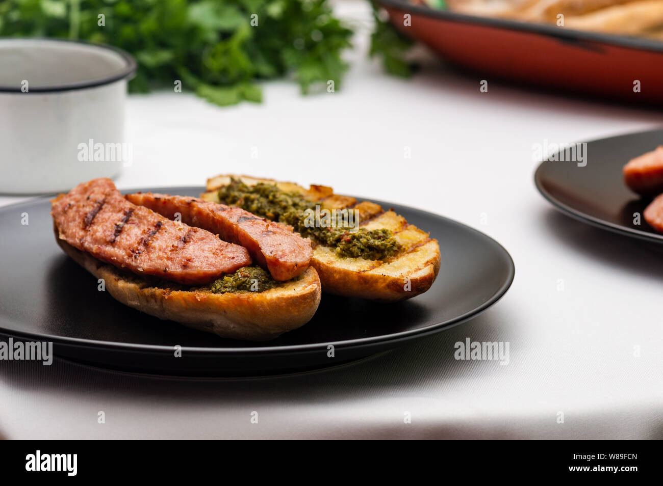 Choripan, south American style chorizo sandwich made with Argentine chorizo sausage with chimichurri, a parsley and olive oil based condiment Stock Photo